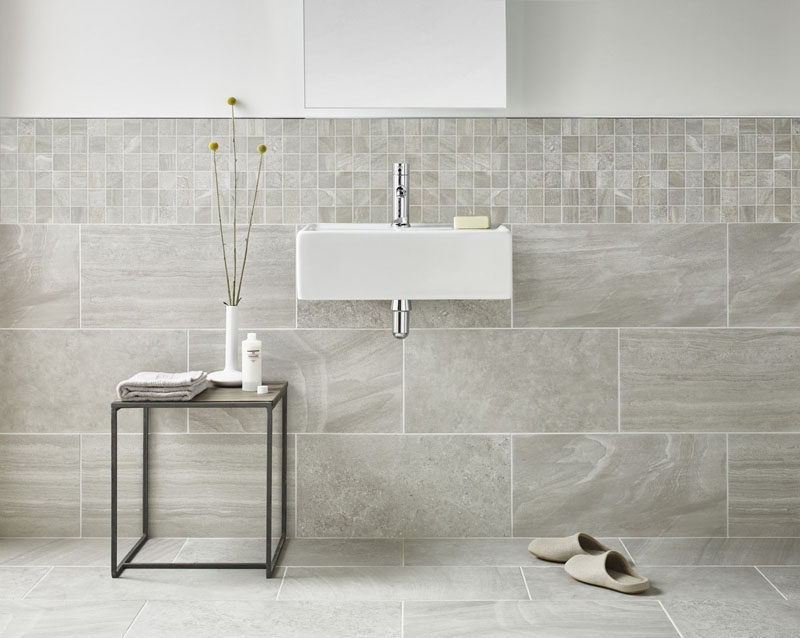 Bathroom Tile Ideas - Use Large Tiles On The Floor And Walls // Large tiles that flow from the floor to the wall, together with smaller wall tiles that line the bottom half of this bathroom wall, help to create a cohesive look.