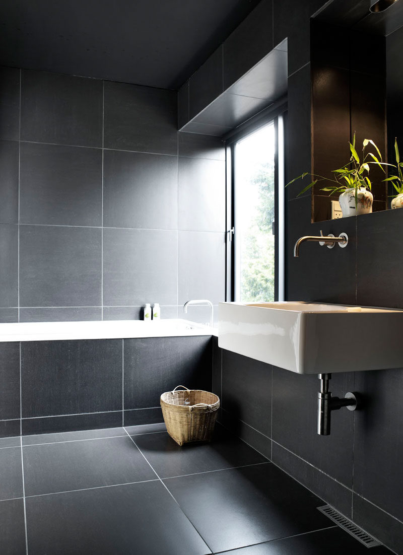 Bathroom Tile Ideas - Use Large Tiles On The Floor And Walls // The use of white grout around these large dark tiles works well because the grout doesn't take over the bathroom - the tiles are large enough to use such contrasting materials without it looking busy or overwhelming.