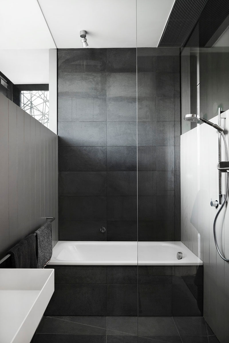 Bathroom Tile Ideas - Use Large Tiles On The Floor And Walls // Large dark tiles cover the floor, bath surround, and back wall of this bathroom, creating a dark dramatic look, but when paired with white walls it creates a sophisticated look.