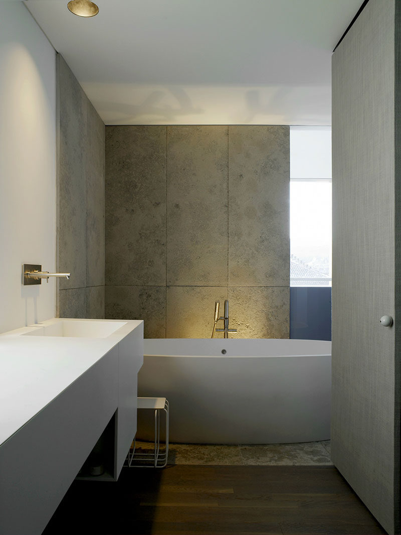 Bathroom Tile Ideas - Use Large Tiles On The Floor And Walls // Large rectangular concrete tiles in this bathroom add an industrial look to the space and help make the room appear taller with their vertical lines.