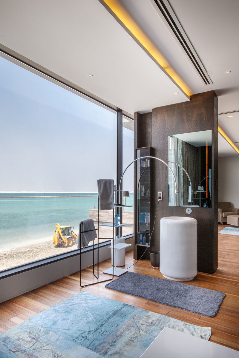 This master bathroom makes the most of the views through the large windows, and hidden lighting runs the length of the ceiling.