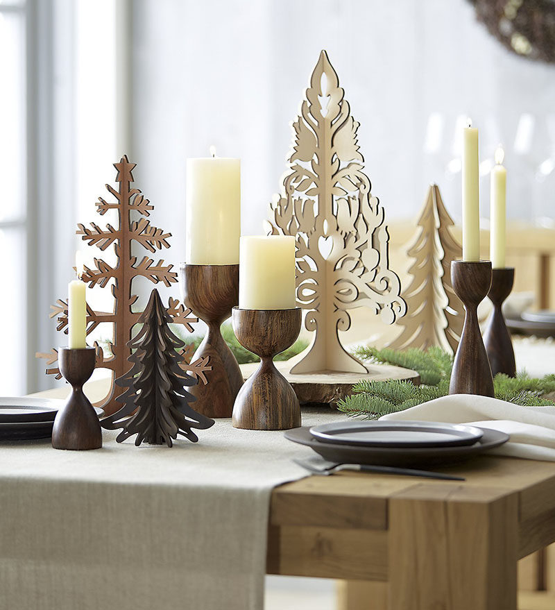 15 Inspirational Ideas For Creating A Modern Christmas Table Full Of Natural Elements // Tall wooden candle sticks mixed in with other wooden decor create a natural yet festive centerpiece you'd be likely to find in a Nordic style home.