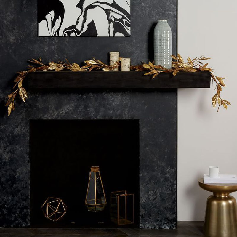 30 Modern Christmas Decor Ideas For Your Home // This gold leaf garland adds a bit of sparkle t this dark mantle and pulls together the other elements of gold in the room.