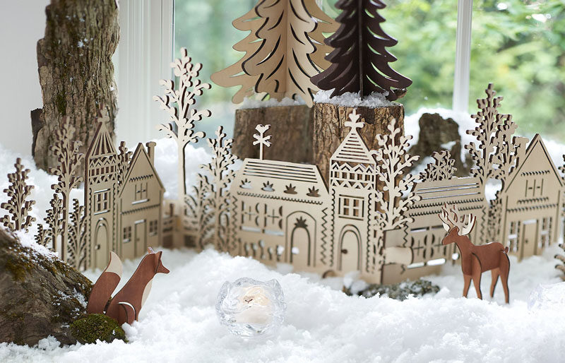 30 Modern Christmas Decor Ideas For Your Home // This intricate wooden village adds a Scandinavian element to your scene and helps keep your decor feeling natural.