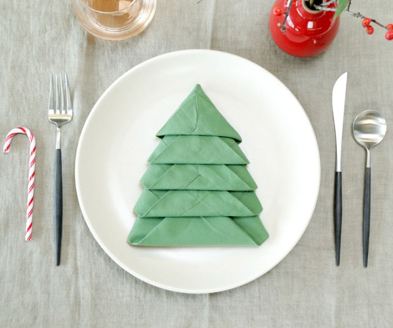 15 Inspirational Ideas For Creating A Modern Christmas Table Full Of Natural Elements // Folding your napkins into the shape of Christmas trees and including a candy cane makes for a fun place setting that grown ups and children alike will enjoy.