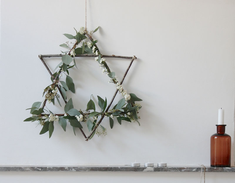 21 Modern Wreaths To Decorate Your Home With This Holiday Season // This star wreath made from twigs and natural greenery creates a Scandinavian Christmas feel and would work on any door or above any mantle.