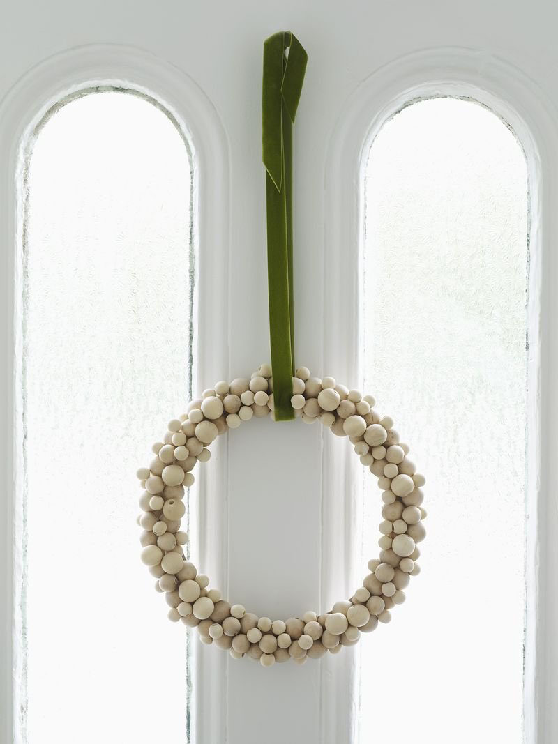 21 Modern Wreaths To Decorate Your Home With This Holiday Season // Gluing wood beads to a wreath form is an easy way to create a Nordic looking wreath that can either be left with its natural finish or painted festive colors.