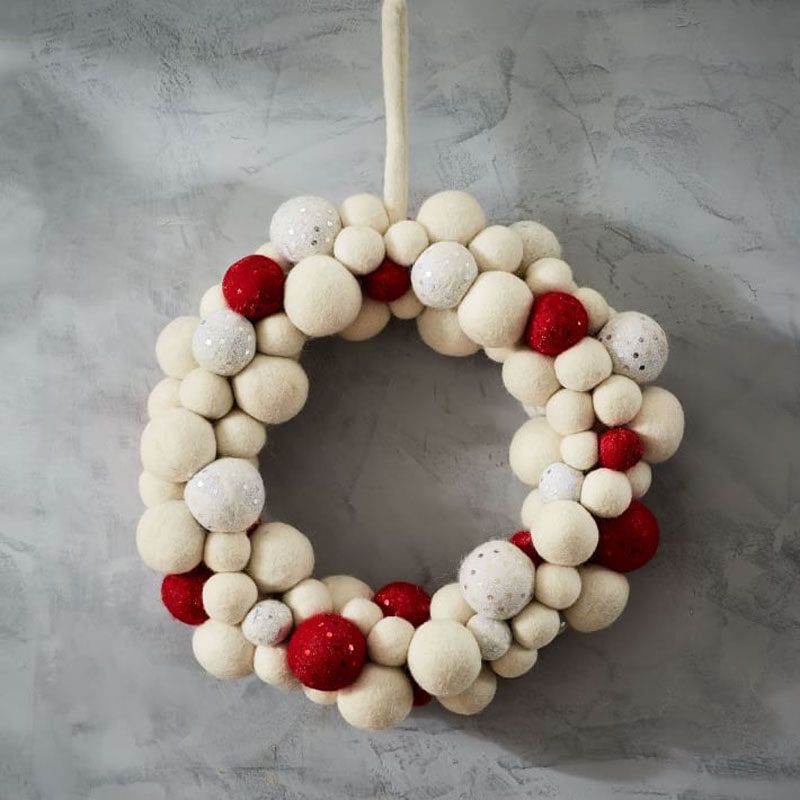 21 Modern Wreaths To Decorate Your Home With This Holiday Season // The felt balls in various holiday colors on this modern wreath make it the perfect addition to the front door.