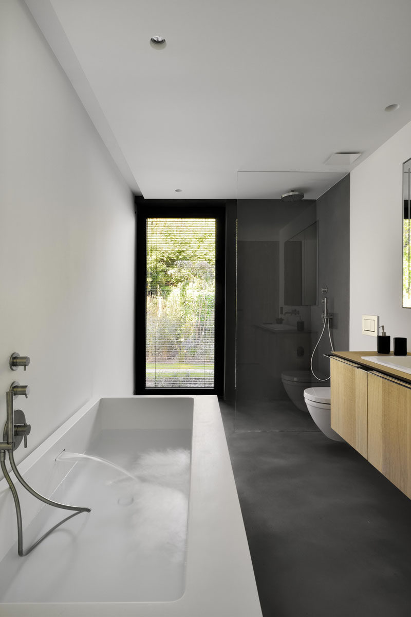 This modern guest bathroom has a gray, white and wood palette.