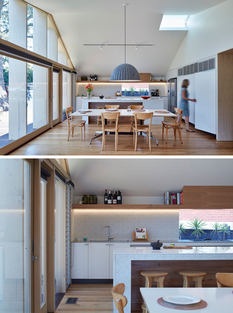 Inside the extension of this Australian home, the pitched ceiling and white walls make the space appear bright and large. At one end is the kitchen and the dining room.