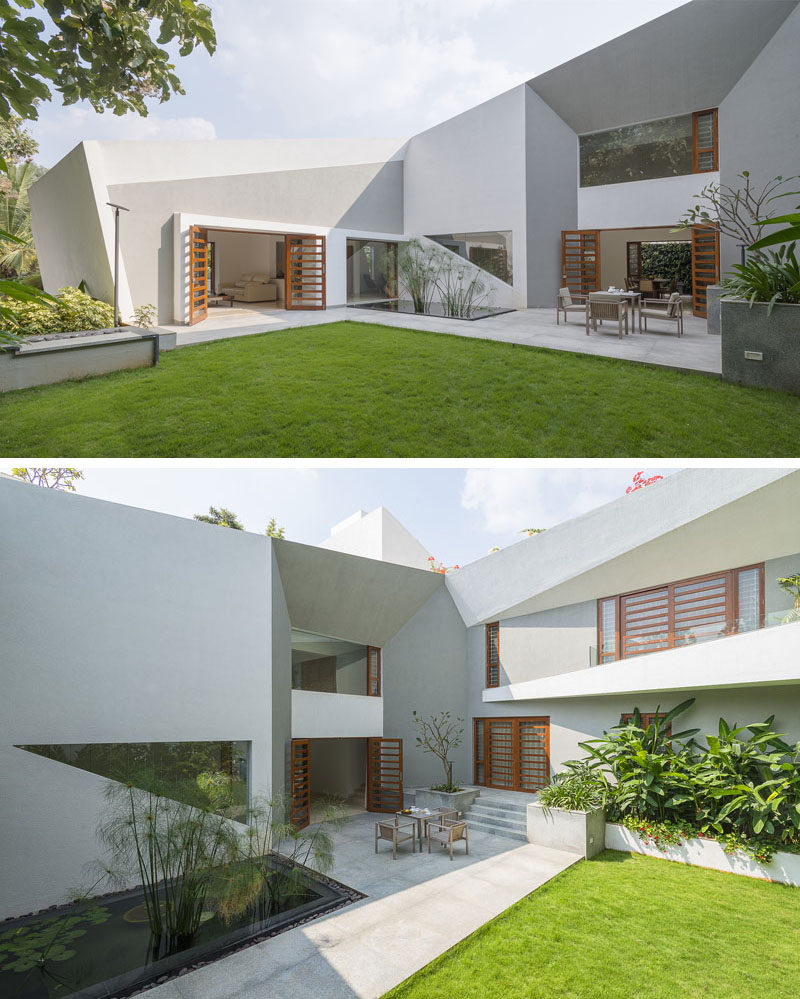 The landscaped backyard of this modern home has a large grassy area with a water feature and two patio areas that connect.
