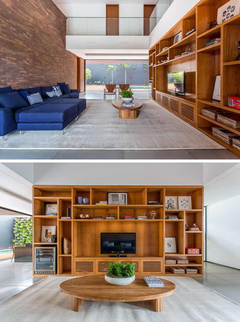 In this living room a large wooden shelving unit fills the space perfectly, and on the opposite wall, bricks have been used as a feature wall behind the sofa.