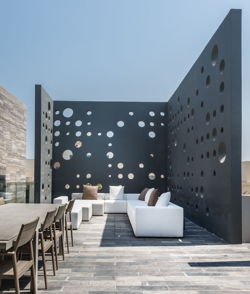 This home has a rooftop deck with lounge and outdoor dining area that's surrounded by perforated walls for privacy.