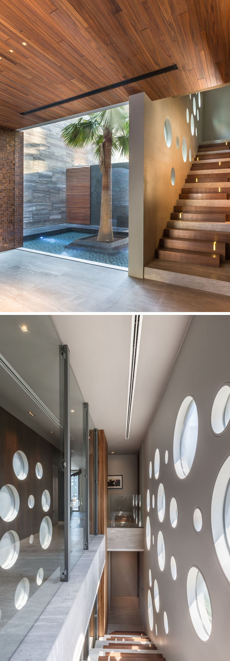 Large circular windows in the wall provide natural sunlight to the staircase.