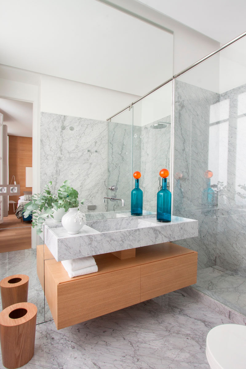 Bathroom Design Ideas - Open Shelf Below The Countertop // The wood used on the shelf in this bathroom is the same wood used on the walls and floor of the bedroom, creating a cohesive look and helping to warm up the marble used throughout the rest of the bathroom.