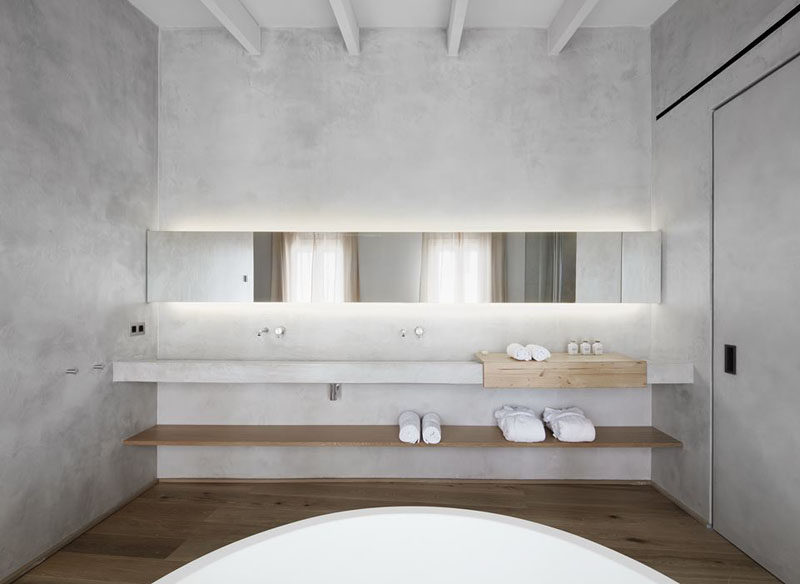 Bathroom Design Ideas - Open Shelf Below The Countertop // The long wood self under the counter of this minimalist bathroom creates a place to store bathroom supplies and adds an element of depth to the space.