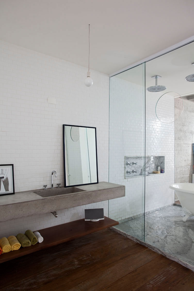 Bathroom Design Ideas - Open Shelf Below The Countertop // The wooden shelf under the concrete countertop provides a dry place to keep things you don't want getting wet, like towels and speakers.