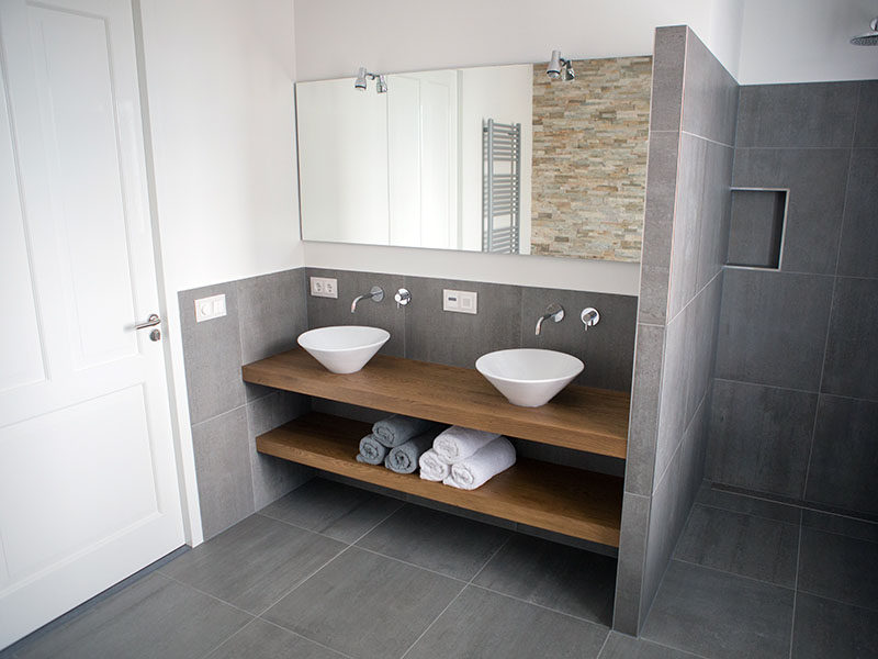Bathroom Design Ideas - Open Shelf Below The Countertop // This bathroom predominantly covered in stone tiles but is warmed up with the wood counter and shelf that give it a modern and inviting look.