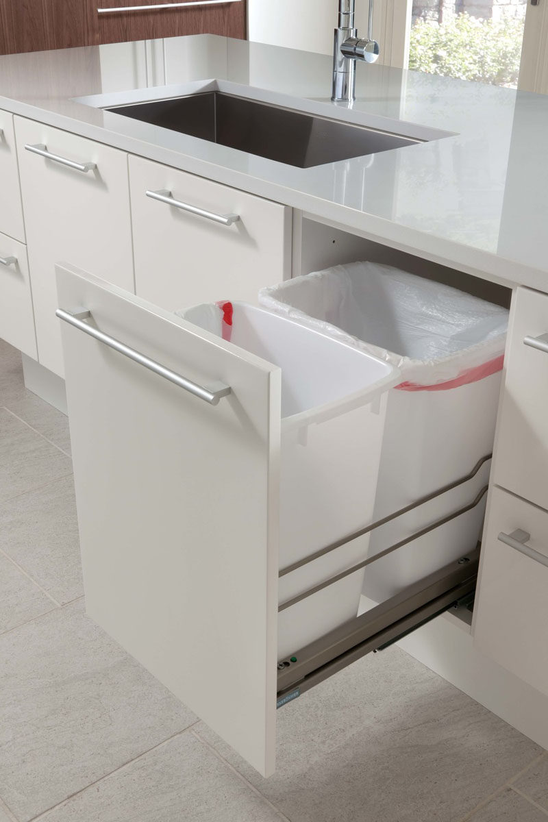 Kitchen Design Idea - Hide Pull Out Trash Bins In Your Cabinetry // These trash bins sit on the pull out shelf next to the sink where much of the food prep is done, making it easy to wipe food remnants off the counter and into the bin.