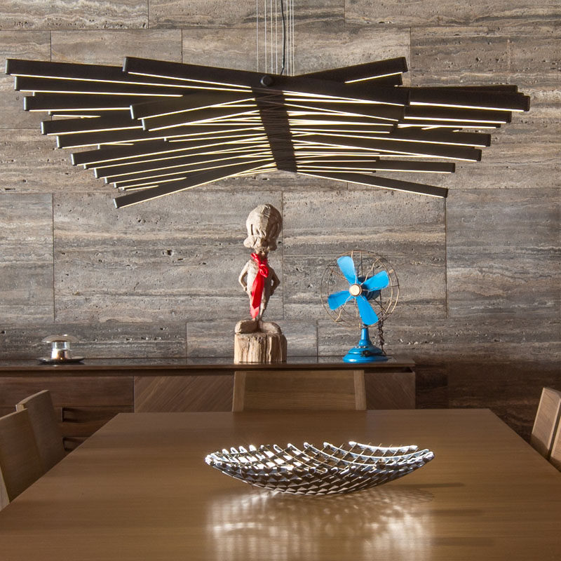 A sculptural light hangs directly above this dining table, while a wall of silver grey travertine runs the length of the home.