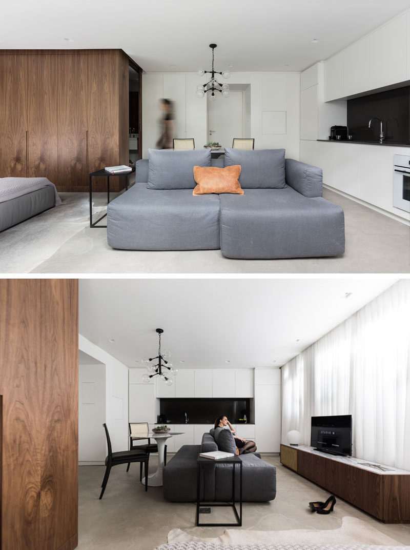 In this small apartment ,the entry, kitchen, living, dining and bedroom all share the same area. The living room had a custom sofa designed to fit the space, and a long tv cabinet provides extra storage.