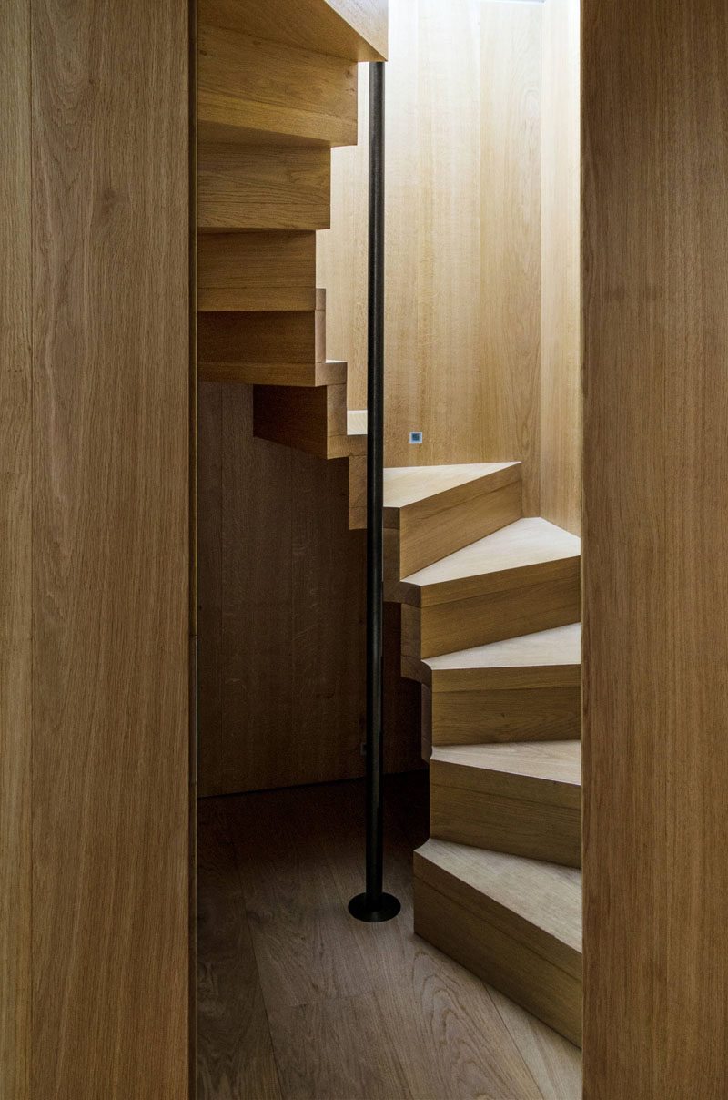13 Stair Design Ideas For Small Spaces // These compact wooden stairs spiral up around a black pole that you can hang onto as you climb up and down for a bit of extra safety and support.