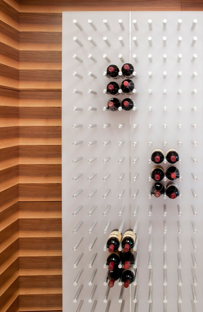 Wine Rack Ideas - Show Off Your Bottles With A Wall Mounted Display // The pegs on this wall can support hundred of bottles of wine for a packed look or just hold a few for a more open and floating look.