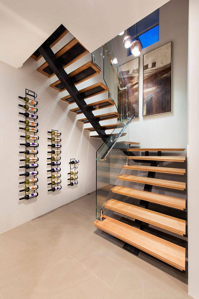 Wine Rack Ideas - Show Off Your Bottles With A Wall Mounted Display // The staggered heights of these three wine racks follow the line of the staircase and create a simple display for all the wine bottles.