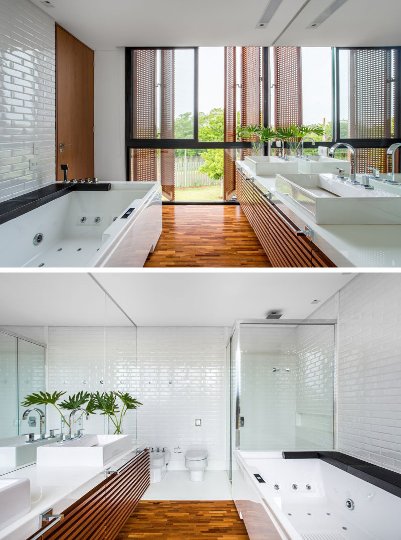 This bathroom has a wood and white palette with wooden floors, door, cabinetry and shutters, while the tiles, sinks, countertop and bath have been kept white.