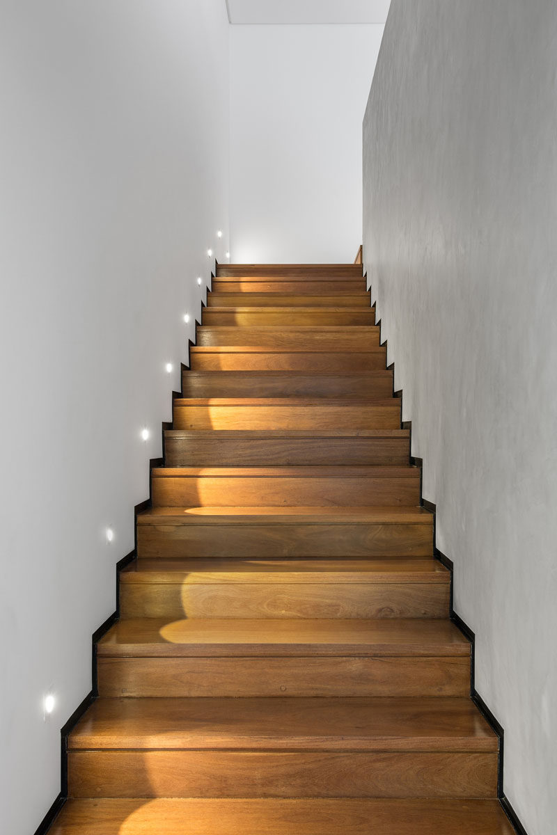 Wooden stairs with black metallic skirting boards and lighting, lead you to the upper floor of this home.