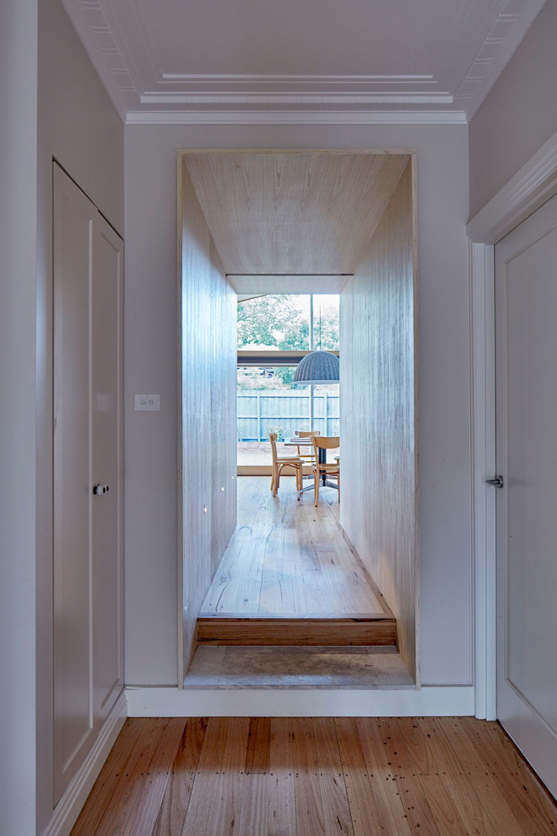 This wood covered hallway defines the entrance to the extension that was added to this Australian home.