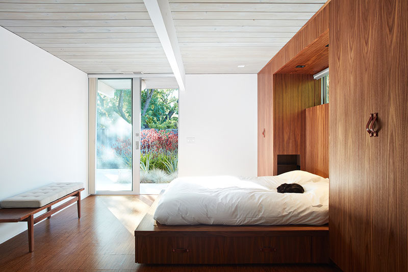 In this remodeled master bedroom, the bed now sits on a platform that's tucked within a wall of built-in wooden wardrobes with leather handles. By replacing the master closet with these built-ins the designers were able to create a large master bedroom.