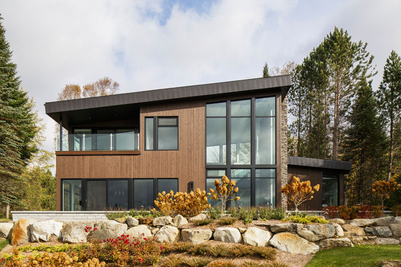 This modern lake house in Canada has an exterior clad in wood, stone, and metal