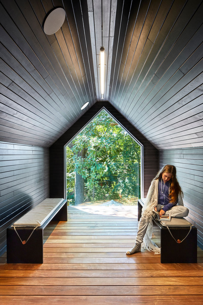 A small wood-lined room has been added into the gable of this contemporary house extension and provides a quiet retreat on the third floor of the home.