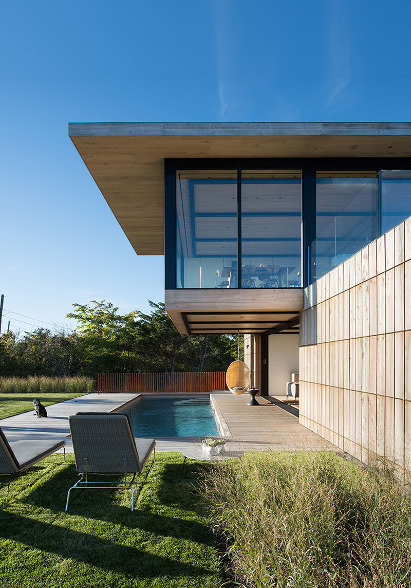 A swinging chair hangs from the cantilevered section of this modern house and a provides a place to relax by the pool.