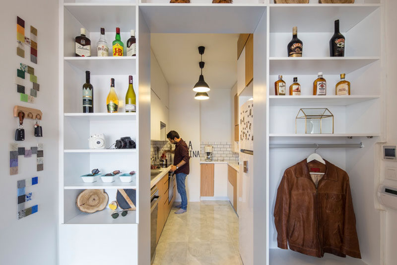 Open shelving surrounds the entrance to this kitchen and provides a place to hang jackets next to the front door.