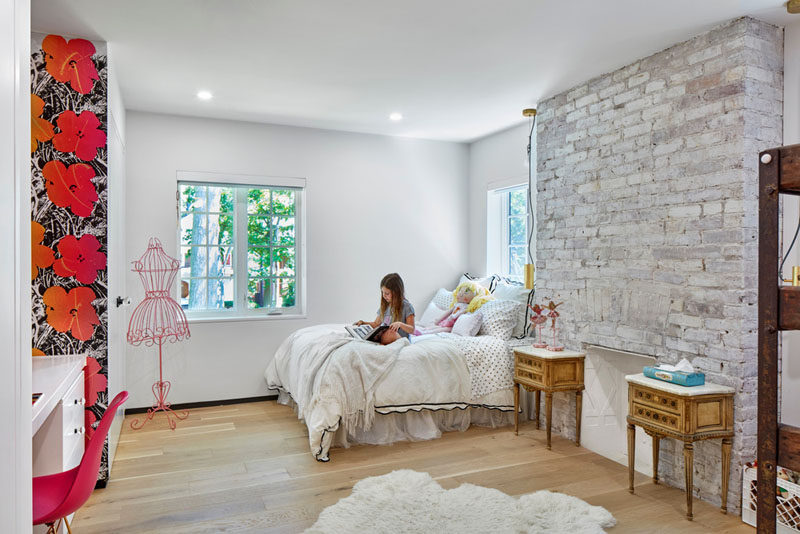 This girls bedroom in a renovated heritage house features the an original fireplace with brick surround.