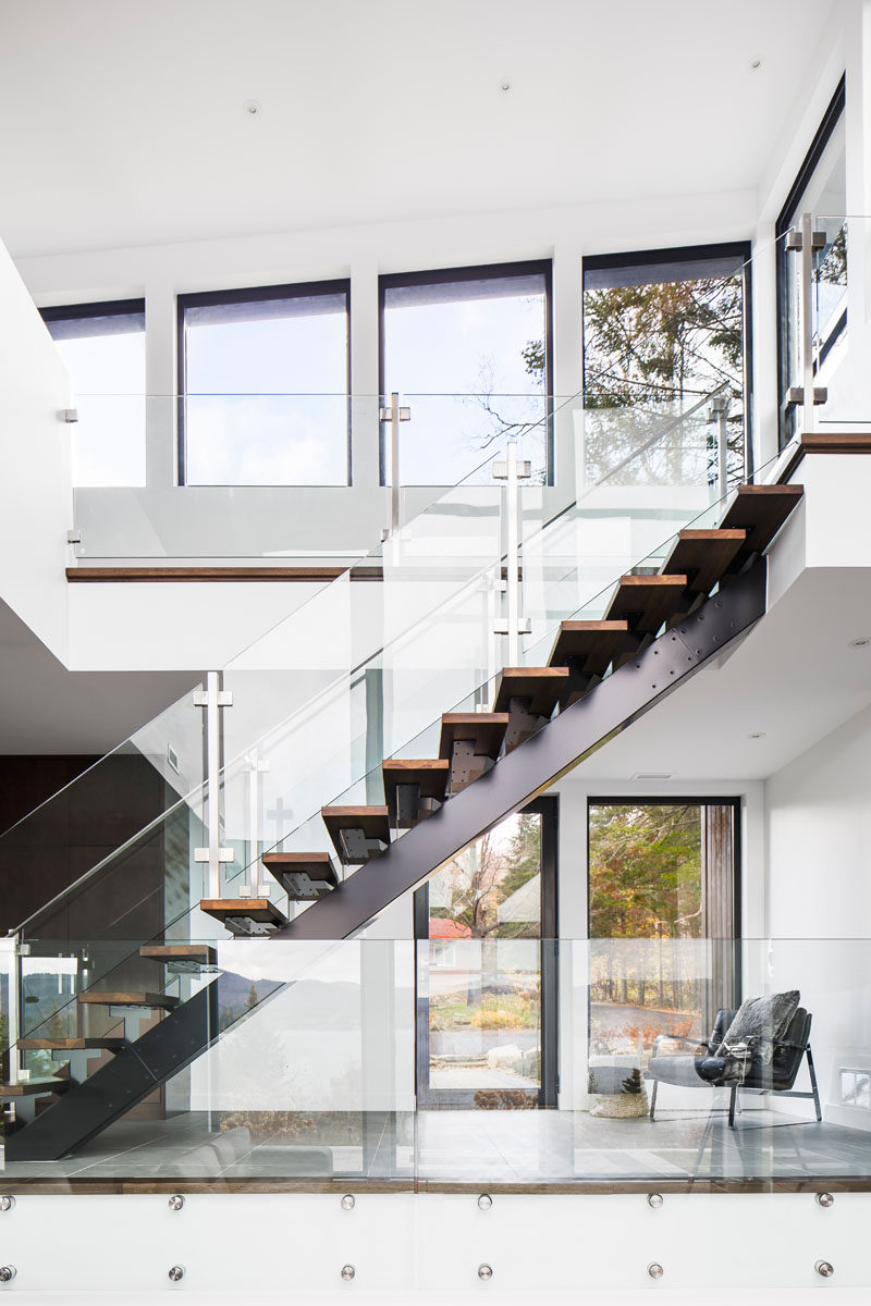 Wood and steel stairs with glass safety railings guide to you the upper level of this modern lakeside home.
