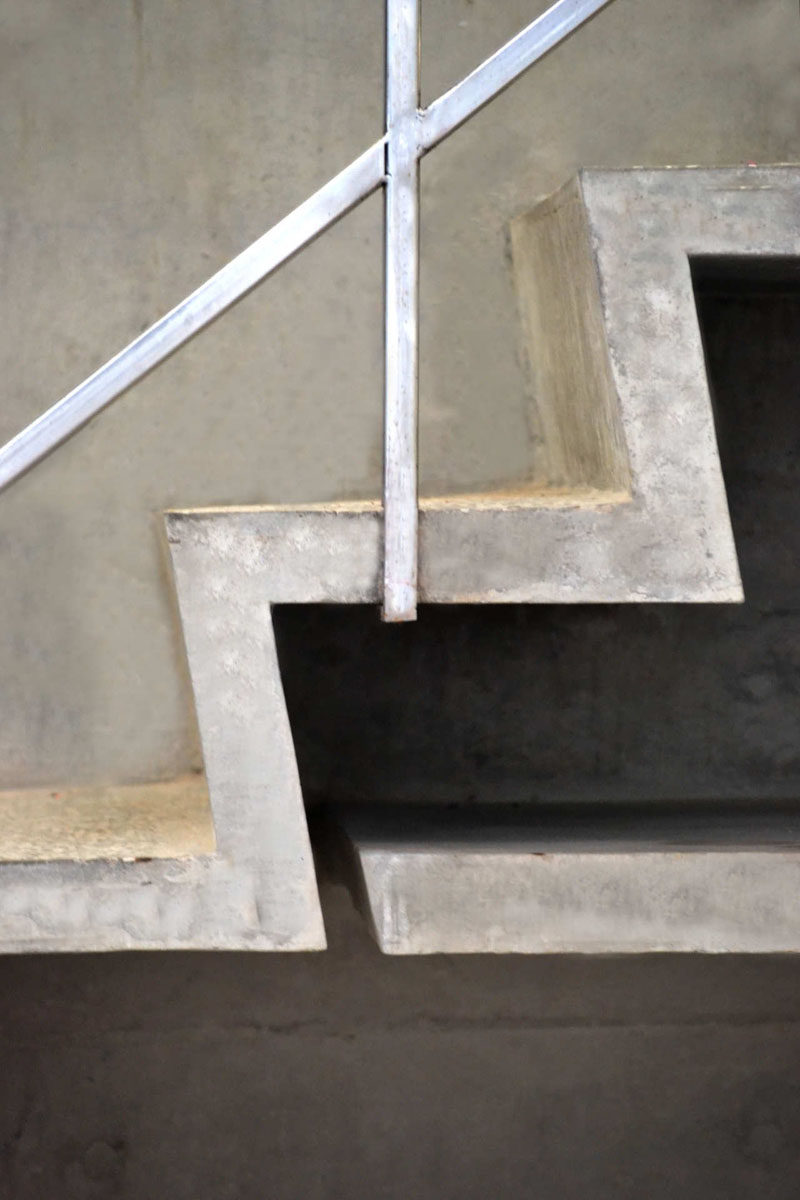 Interior Design Details - Industrial Close Ups // Concrete steps and thin metal handrails give this staircase a simple, modern, industrial look.