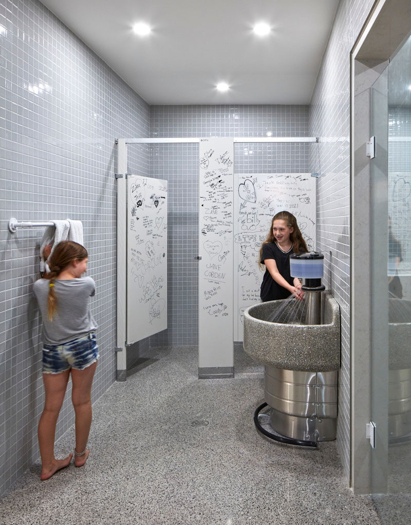 In this home's basement, there's a bathroom that's been modeled after a school washroom and features a classic bathroom stall look with a communal sink that has a foot pedal faucet.