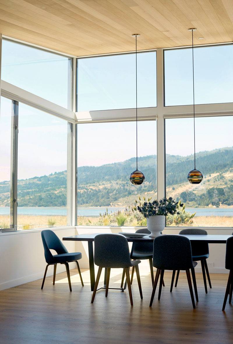 In this dining room, two delicate pendant lamps hang from the ceiling, while the large windows allow for plenty of natural light to fill the interior and they frame the surrounding views.