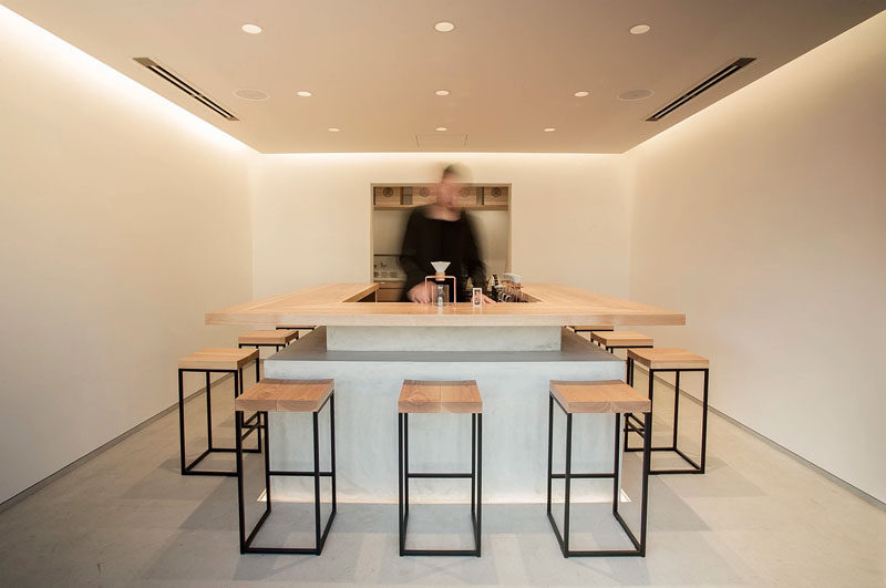 The interior of Tokyo Saryo features a simple bar that sits centered on a concrete floor and is surrounded by stools made from black steel frames and wooden seats. The walls have been left bare and a drop ceiling holds both hidden lighting and six small pot lights to create a soft glow throughout the space.