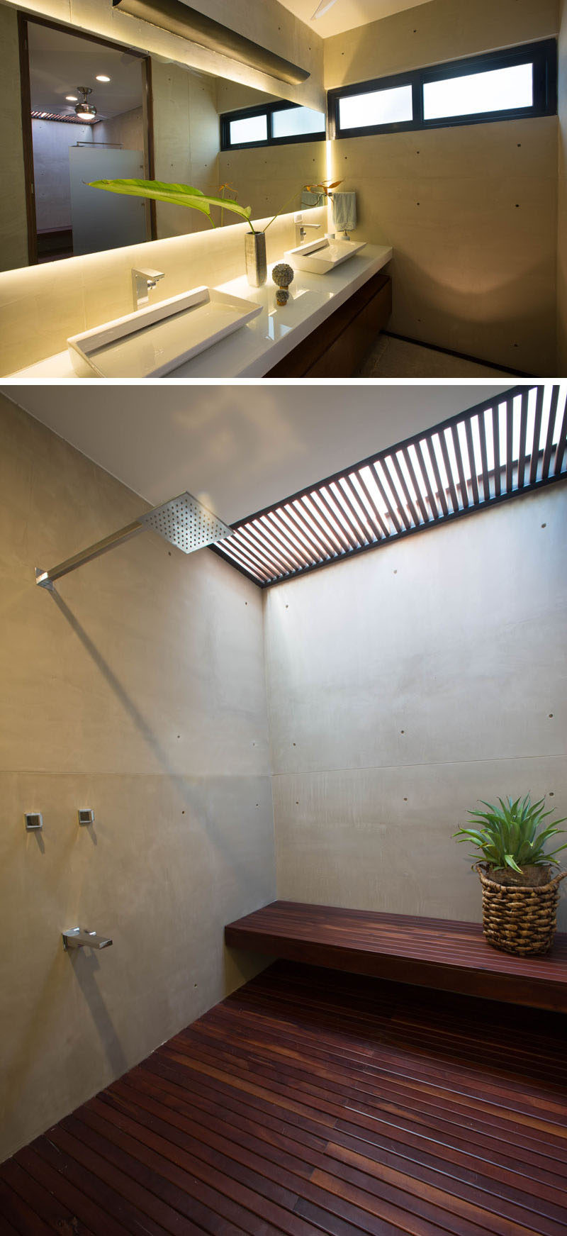 In this bathroom there's a vanity with double sinks and a shower that has a wooden floor, a skylight and built-in bench.