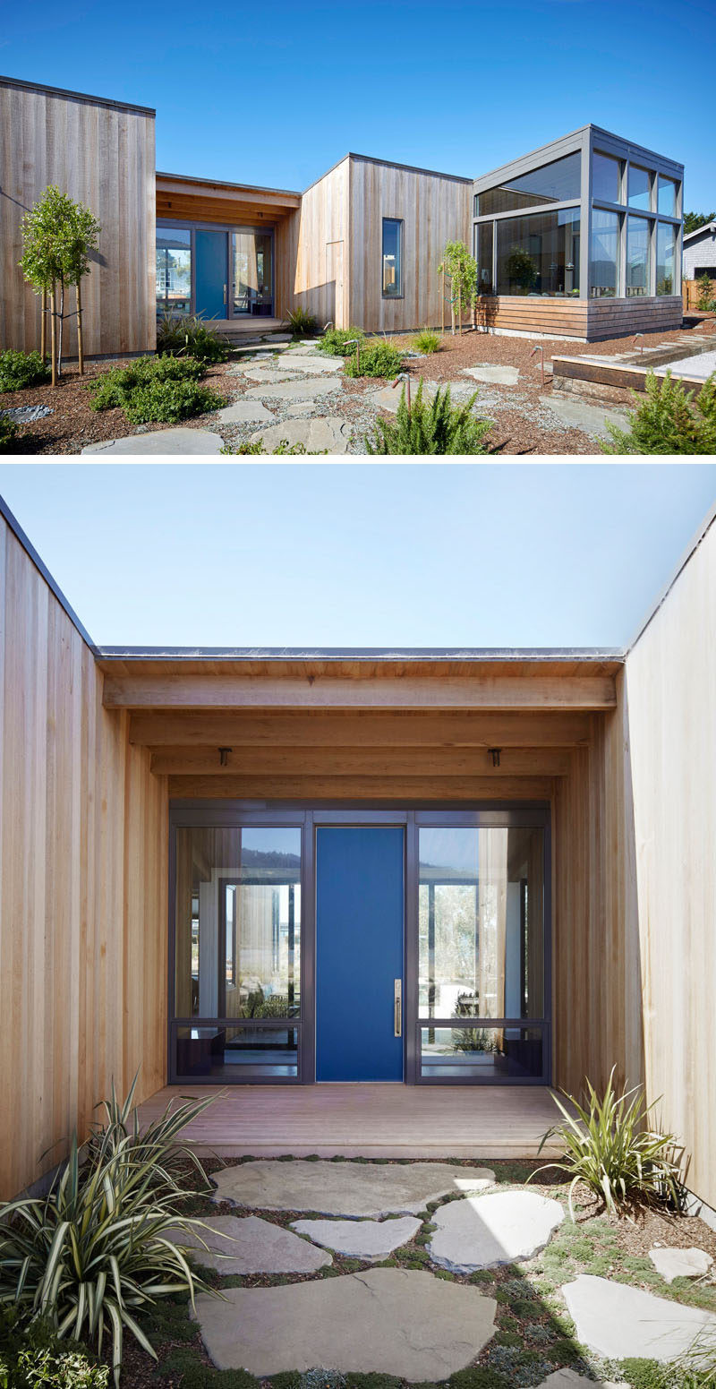 At the front of this house, minimal landscaping with stepping stones guides you to the blue front door that adds a pop of color to the home.