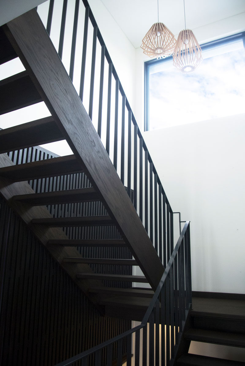 A contemporary dark wood staircase leads you upstairs and a large window floods the space with natural light.