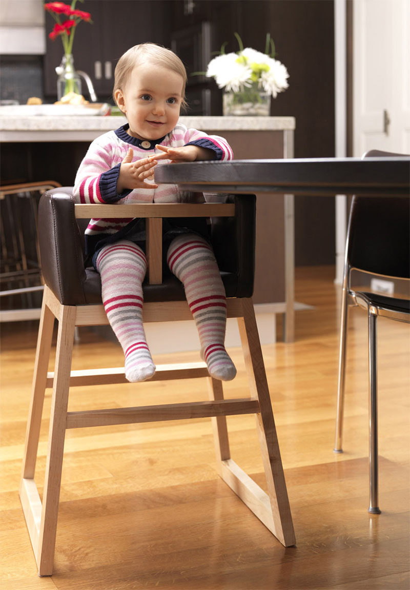14 Modern High Chairs For Children // This dark leather and wood high chair will fit right in with the rest of your sophisticated dining furniture and is short enough to tuck under the table when it isn't being used.