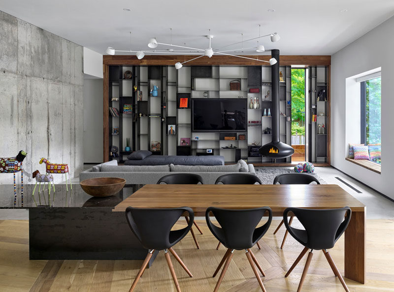 In this interior, a long dining table divides the open floor plan. On one end is the family room with a custom designed metal metal bookcase by Commute Design, and a suspended black wood-burning fireplace.