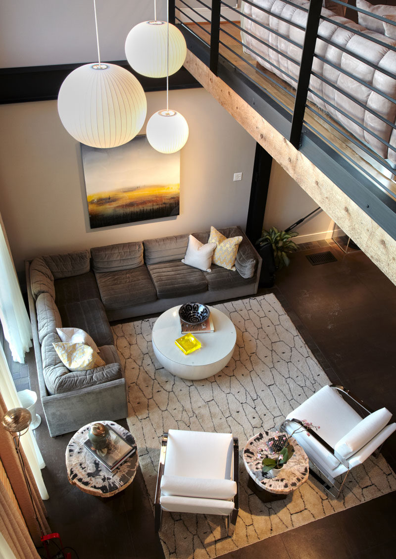 Interior Design Ideas - 17 Modern Living Rooms As Seen From Above | Warm tones give this industrial loft a cozy feel while the tall window keeps it bright and open.