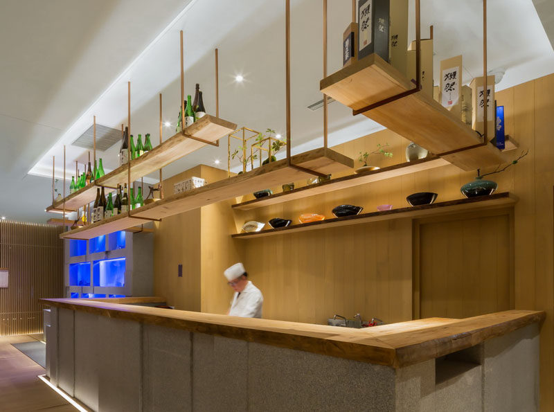 Restaurant Interior Design Ideas - This restaurant's bar has hanging wooden shelving to match the live edge wooden bar top.
