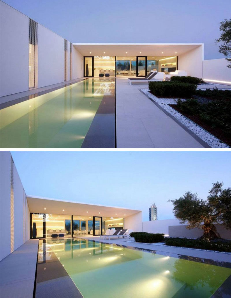 15 Single Story Modern Houses | The touches of black on the exterior of this all white single level house create a dramatic contrast that's made even more dramatic with the help of the lights in the pool and near the fence.